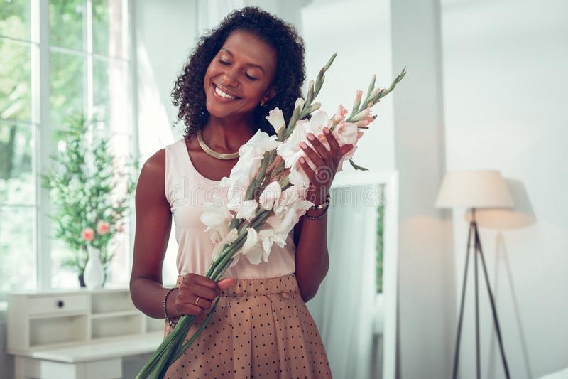 Härlig Afro--amerikan kvinna som tycker om den härliga buketten av gladioluses arkivbild