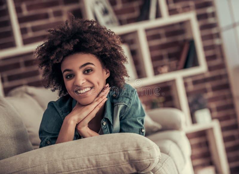 Härlig afro- amerikansk flicka hemma arkivbild