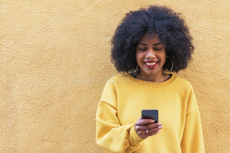 Härlig afro amerikansk kvinna som använder mobilen i gatan royaltyfri bild