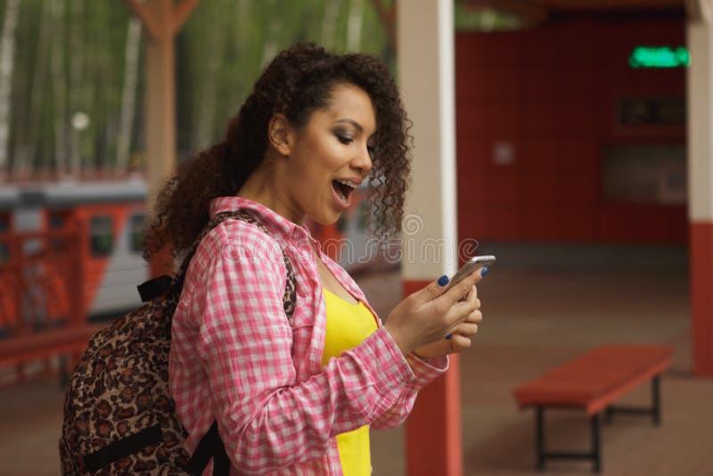 Härlig afro amerikansk kvinna som använder mobilen i gatan Kommunikation royaltyfria bilder