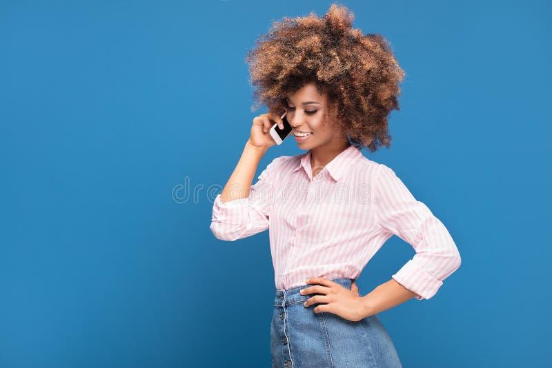 Härlig afro dam som talar vid mobiltelefonen arkivfoton