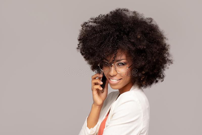 Härlig afro kvinna som talar vid mobiltelefonen arkivfoto
