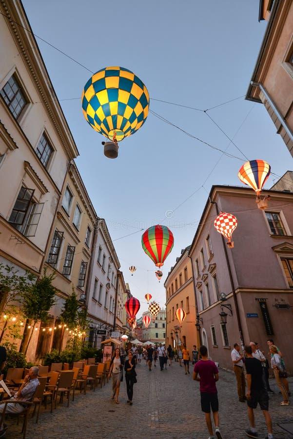 Härlig aftongata, glödande ballonger och gamla ljusa byggnader i den gamla staden av Lublin, Polen royaltyfria foton