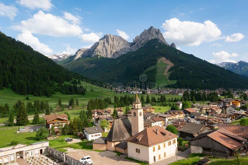 Härlig alpin by med katolska kyrkan på förgrunden Val di Fassa Italien fotografering för bildbyråer