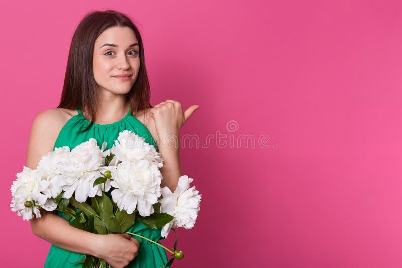Härlig angenäm ung kvinnlig som ser direkt på kameran, le som är sött som aback gör gest med hennes tumme och att rymma stort royaltyfria bilder
