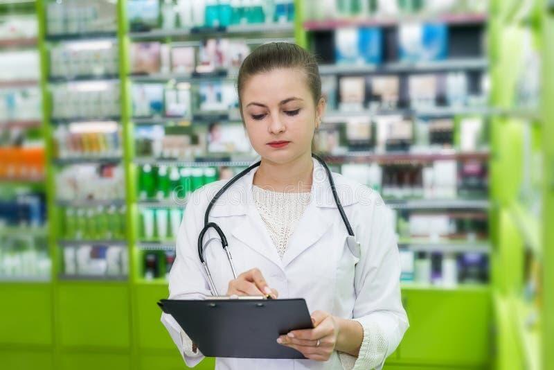 Härlig apotekare som kontrollerar droglistan på minnestavlan royaltyfri fotografi