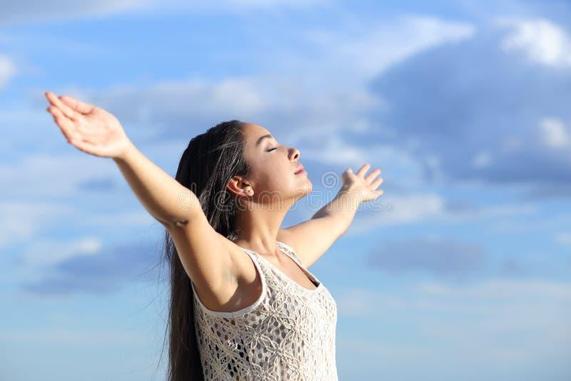 Härlig arabisk kvinna som andas ny luft med lyftta armar arkivbild