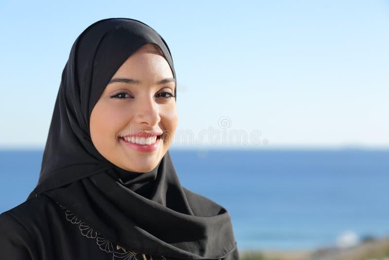 Härlig arabisk saudierkvinnaframsida som poserar på stranden arkivfoto