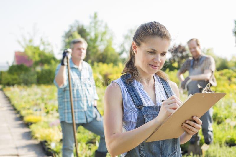 Härlig arbetsledarehandstil på skrivplattan med trädgårdsmästare som står i bakgrund på växtbarnkammaren arkivfoton