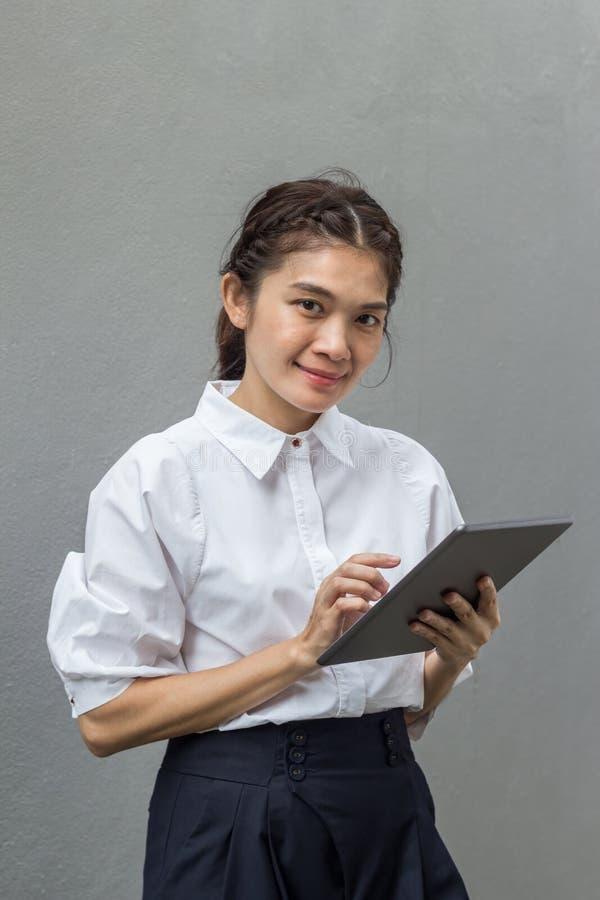 Härlig asiatisk affärskvinna som ler, medan genom att använda minnestavlan arkivbilder
