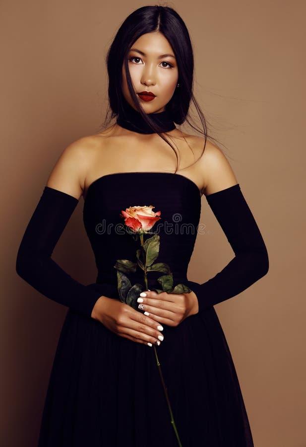 Härlig asiatisk blickflicka med svart hår som bär den eleganta klänningen royaltyfria bilder