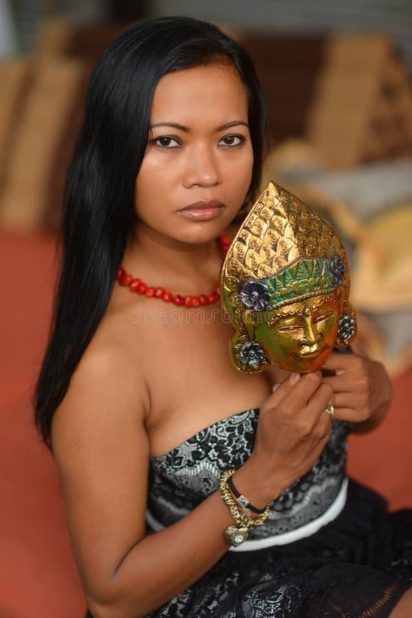 Härlig asiatisk brunettmodell med den traditionella maskeringen från Bali arkivfoto