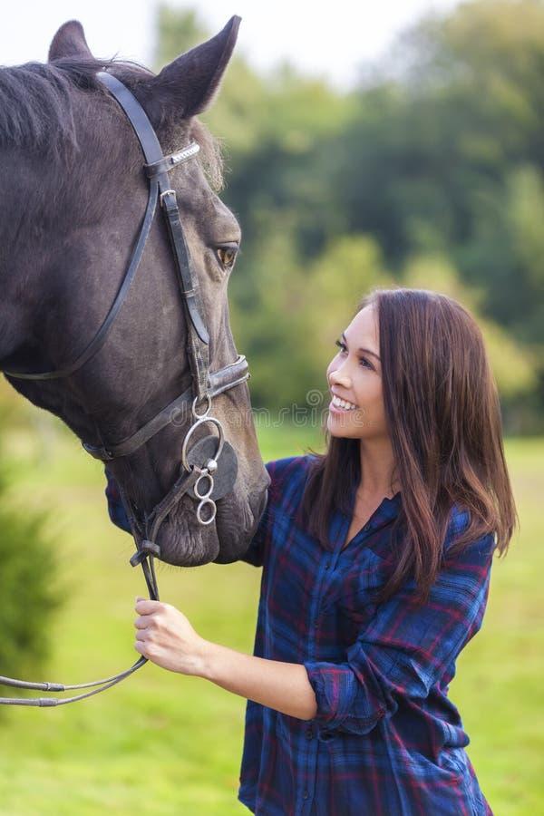 Härlig asiatisk Eurasianflickakvinna med hennes häst royaltyfri foto
