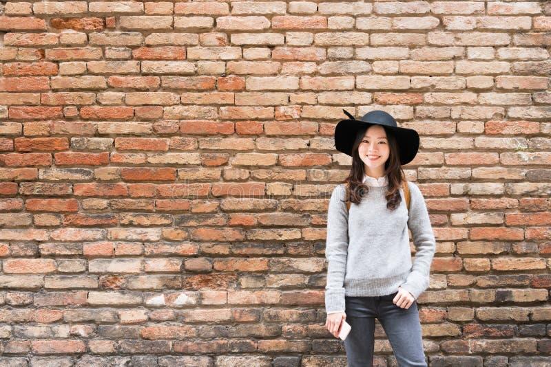 Härlig asiatisk flicka i den trendiga klänningen som framme står av bakgrund för vägg för röd tegelsten med kopieringsutrymme fotografering för bildbyråer