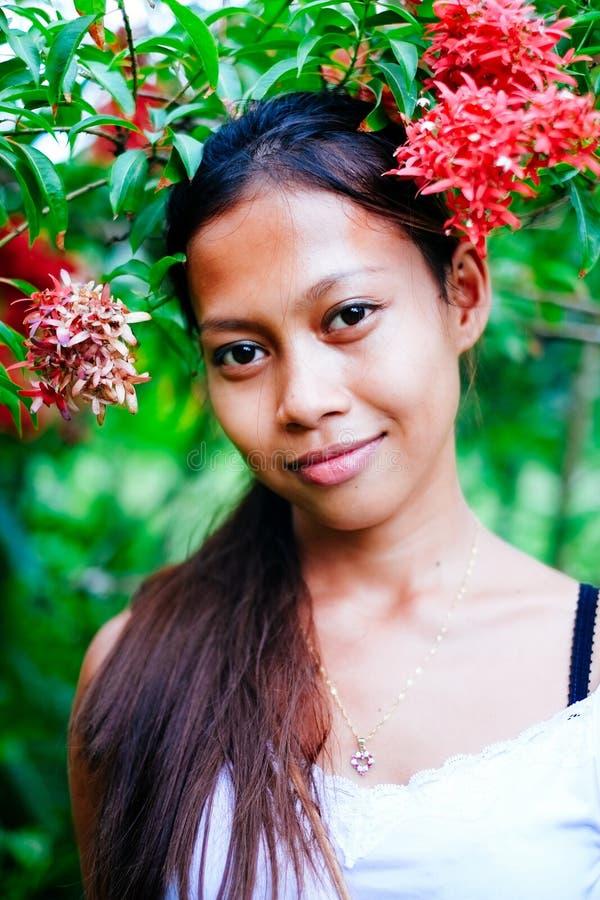Härlig asiatisk flicka i trädgården med blommor royaltyfria bilder