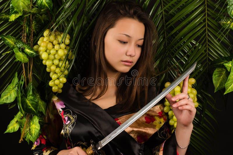 Härlig asiatisk flicka med ett svärd arkivbild