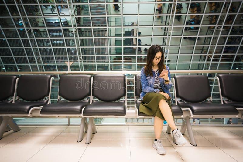 Härlig asiatisk flicka som använder smartphonen som väntar för att stiga ombord flygplanet som är begreppsmässigt arkivbild