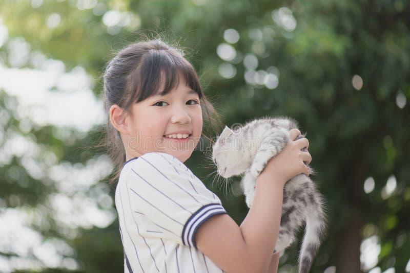 Härlig asiatisk flicka som rymmer den älskvärda kattungen arkivbilder