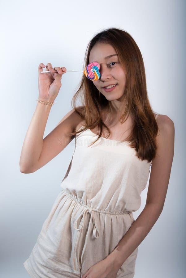 Härlig asiatisk flicka som rymmer en klubba med glädje royaltyfria foton