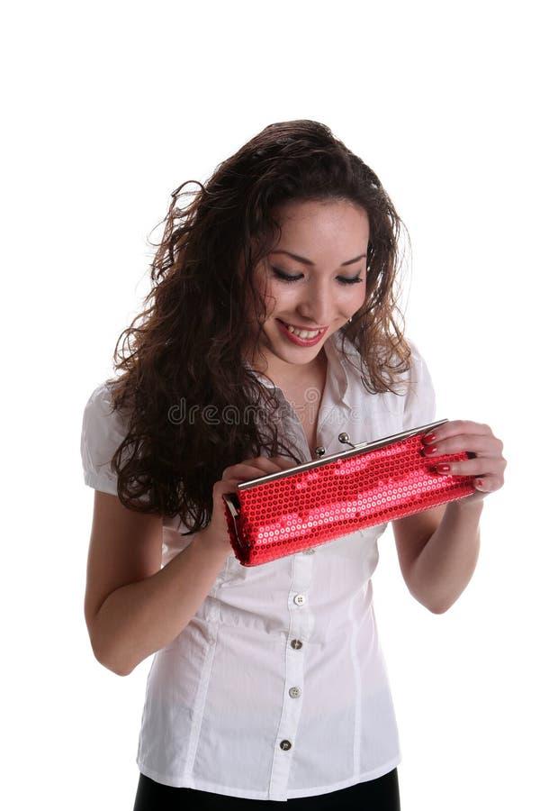 Härlig asiatisk flicka som ser in i den röda handväskan royaltyfria foton