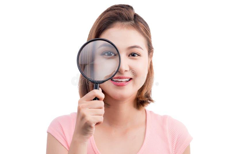 Härlig asiatisk flickastående som ser till och med förstoringsapparaten isolate royaltyfri fotografi