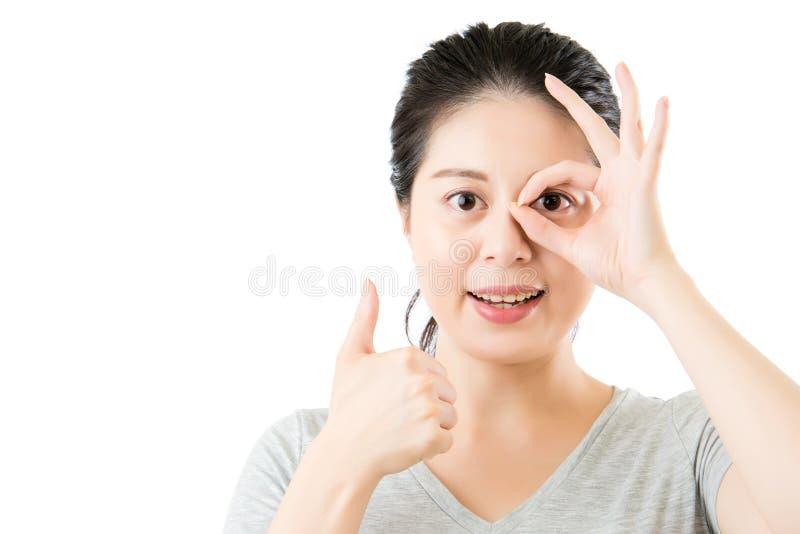 Härlig asiatisk gest och tummar för kvinnashowok upp arkivbilder