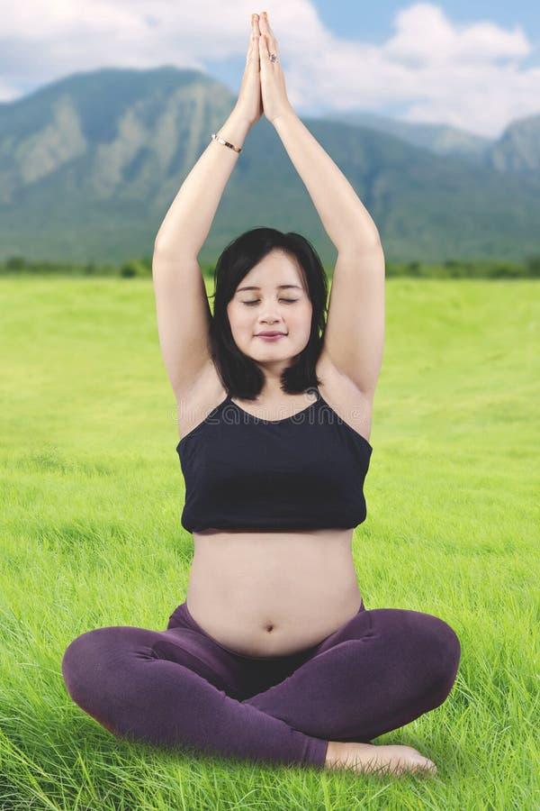 Härlig asiatisk gravid kvinna som mediterar på ängen royaltyfri foto