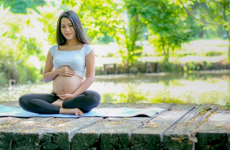 Härlig asiatisk gravid kvinnablick framåtriktat, medan sitt på mattt på träbron och också att trycka på hennes buk med morgonljus royaltyfri foto