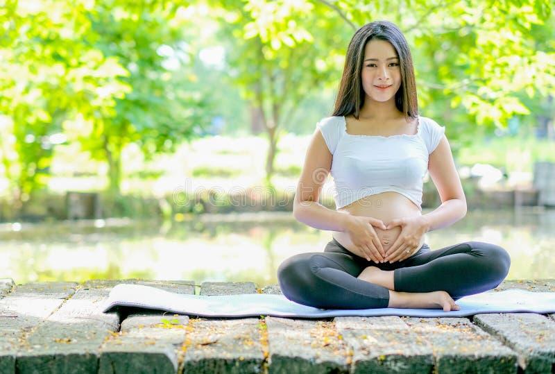 Härlig asiatisk gravid kvinnablick framåtriktat, medan sitt på mattt på träbron och också att trycka på hennes buk med morgonljus arkivfoton