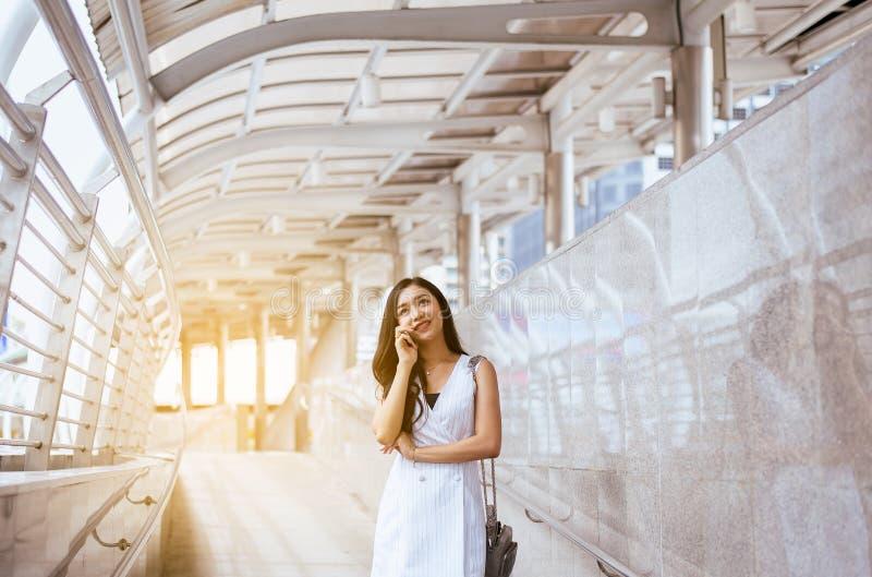 Härlig asiatisk kvinna för stående som använder mobiltelefonen och går i staden, lyckligt kvinnligt förtroende och ler, livsstilb royaltyfri bild