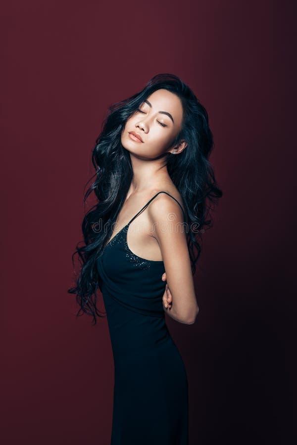 Härlig asiatisk kvinna i den svarta klänningen som poserar i studio royaltyfri fotografi