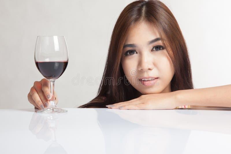 Härlig asiatisk kvinna med den rött vinhanden och hakan på tabellen royaltyfri bild