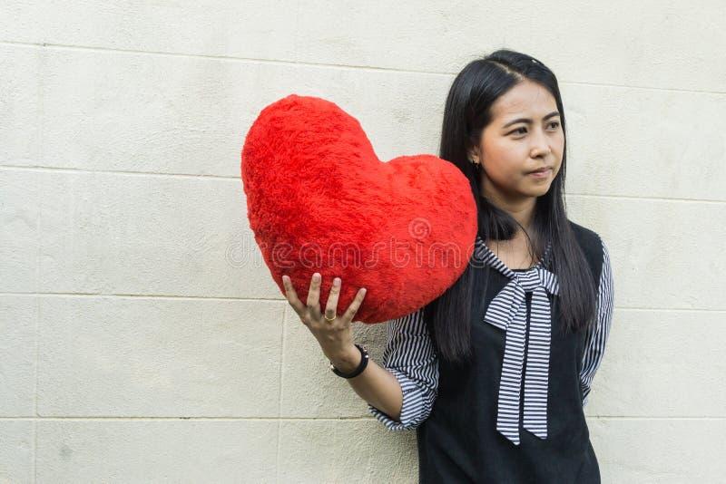 Härlig asiatisk kvinna med en stor röd hjärtaformkudde arkivfoto