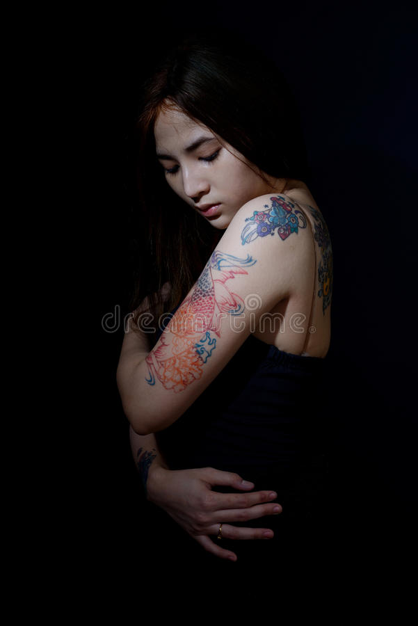 Härlig asiatisk kvinna med tatueringen på hennes arm och skuldra, mörker b royaltyfri bild