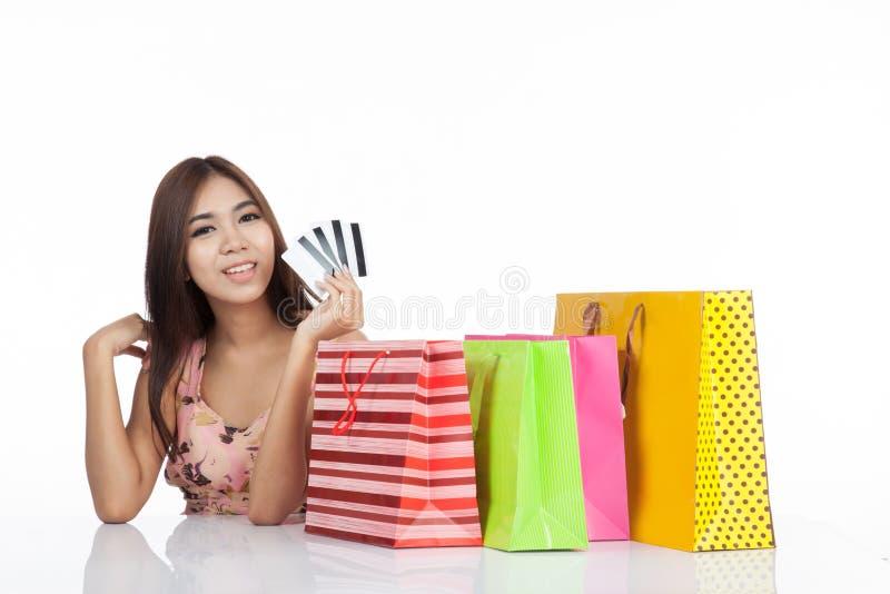 Härlig asiatisk kvinna som är lycklig med kreditkortar och shoppingpåsar arkivbilder