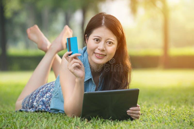 Härlig asiatisk kvinna som använder den digitala minnestavlan som direktanslutet shoppar royaltyfri fotografi