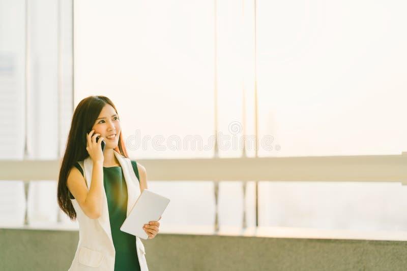 Härlig asiatisk kvinna som använder mobiltelefonen och den digitala minnestavlan på det moderna kontoret, affärskommunikationen e arkivbilder