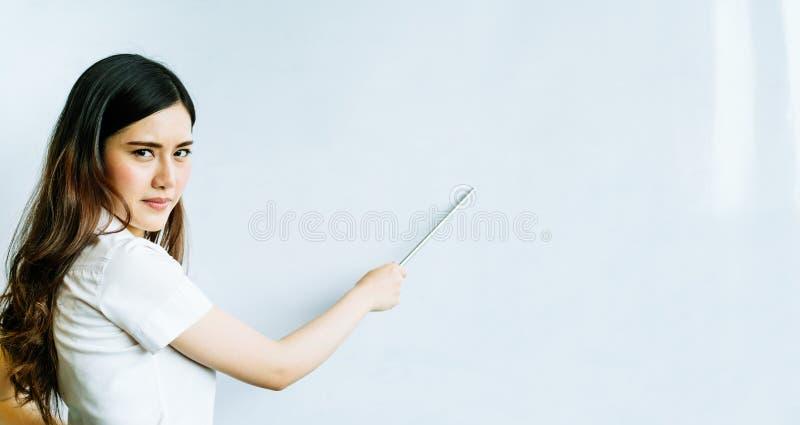 Härlig asiatisk kvinna som använder pekaren på skinande allvarlig eller ilsken framsida för whiteboard, med kopieringsutrymme, fo royaltyfri bild
