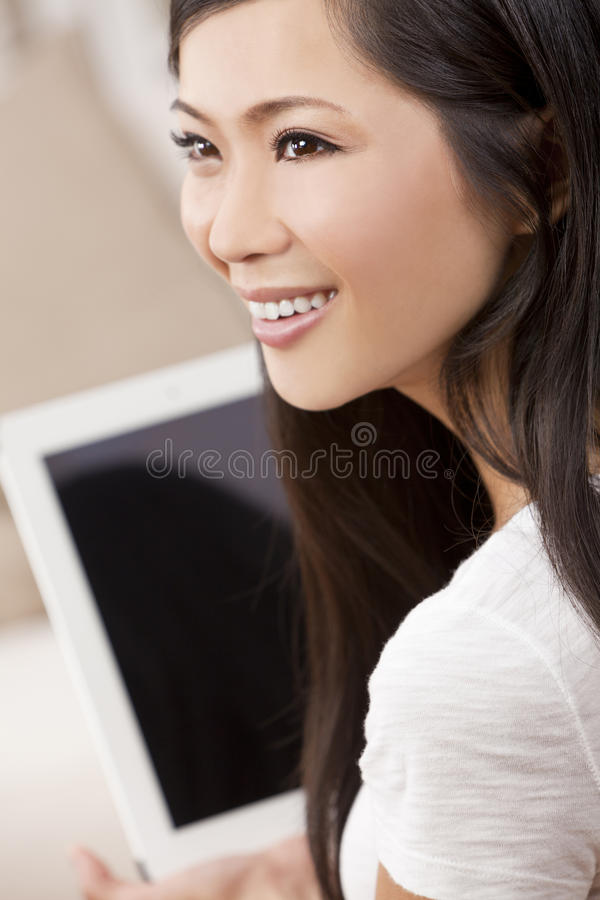 Härlig asiatisk kvinna som använder Tabletdatoren royaltyfri foto