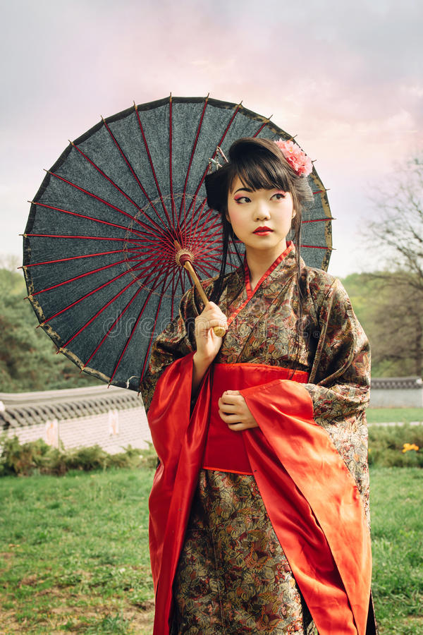 Härlig asiatisk kvinna som går i trädgården royaltyfria bilder