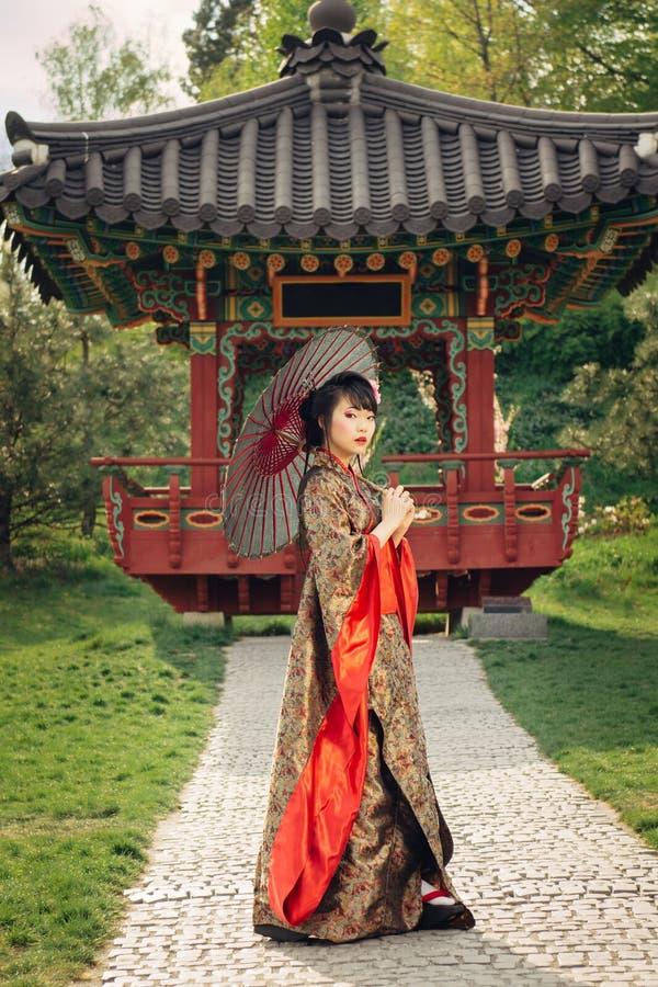 Härlig asiatisk kvinna som går i trädgården arkivbilder