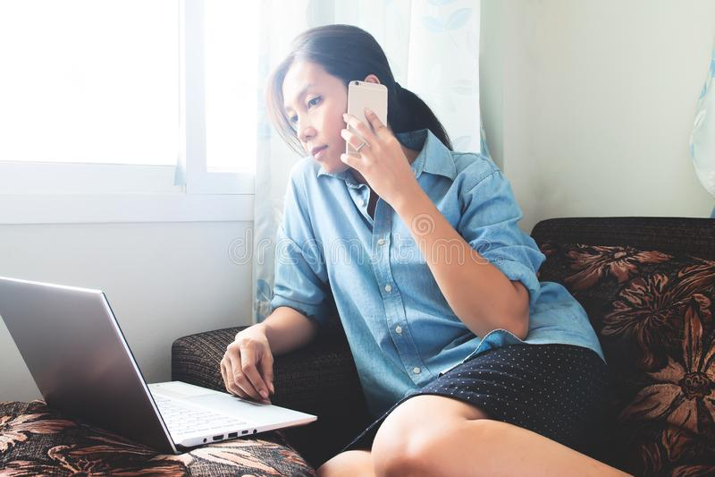 H?rlig asiatisk kvinna som hemma arbetar p? b?rbara datorn Kvinnlig freelancer som f?rbinder till internet via datoren och smartp royaltyfri foto