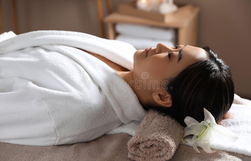 Härlig asiatisk kvinna som ligger på massagetabellen arkivbild