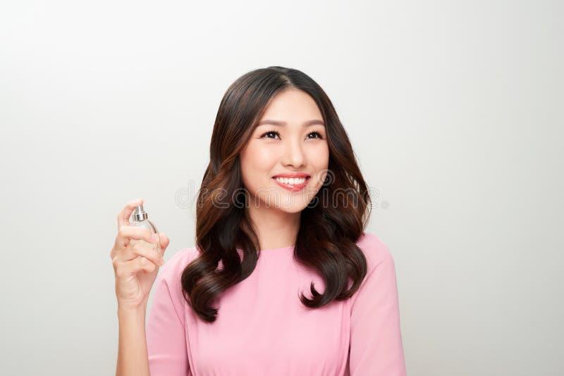 Härlig asiatisk kvinna som rymmer en doftflaska och applicerar den fotografering för bildbyråer