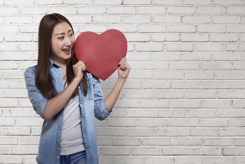 Härlig asiatisk kvinna som rymmer röd hjärta arkivfoto