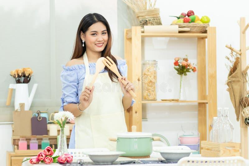 Härlig asiatisk kvinna som rymmer träbestick bak den äta middag tabellen med krukan, maträtten och kitchenware i kökrummet fotografering för bildbyråer