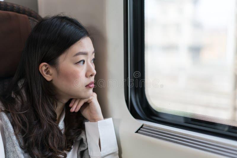 Härlig asiatisk kvinna som ser ut ur drevfönster, med kopieringsutrymme royaltyfri bild