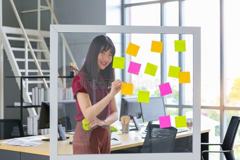 Härlig asiatisk kvinna som skriver färgrikt papper royaltyfria bilder