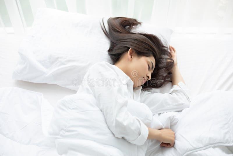 Härlig asiatisk kvinna som värma sig och sover i vit säng royaltyfria bilder