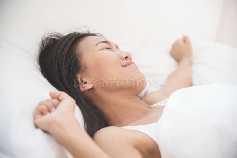 Härlig asiatisk kvinna som vaknar upp på hennes säng arkivbilder